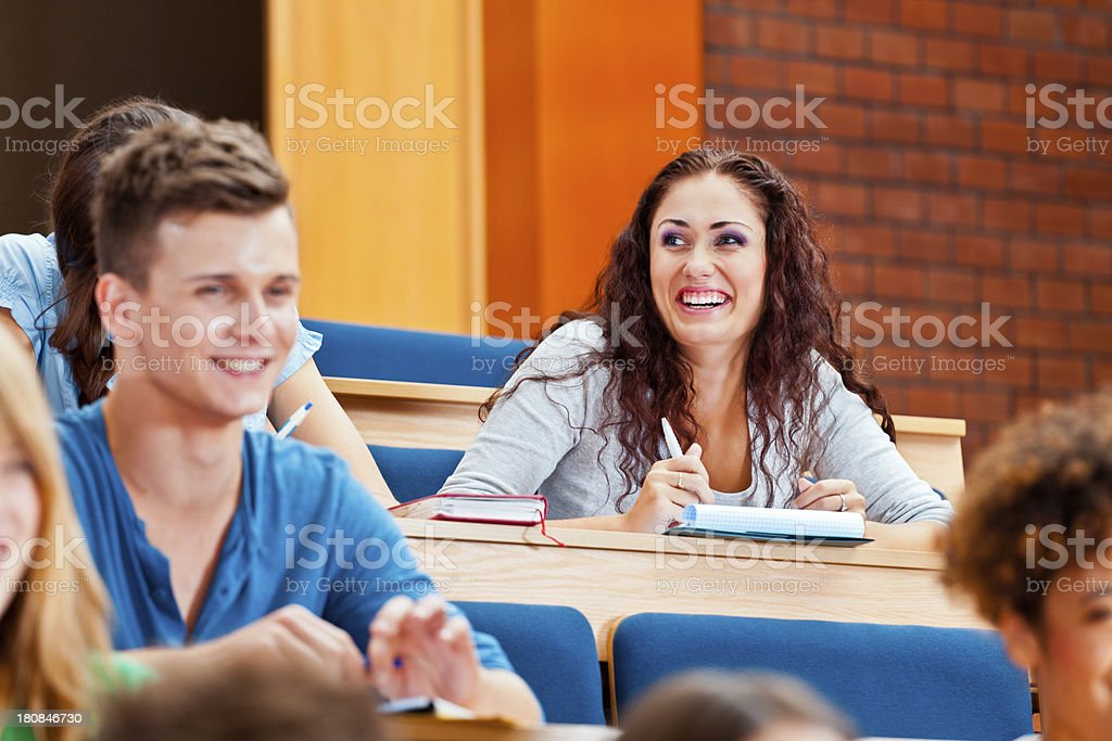 College students at the university College students sitting in the lecture hall at the university and listening to the lecture. Focus on smiling girl. 20-24 Years Stock Photo