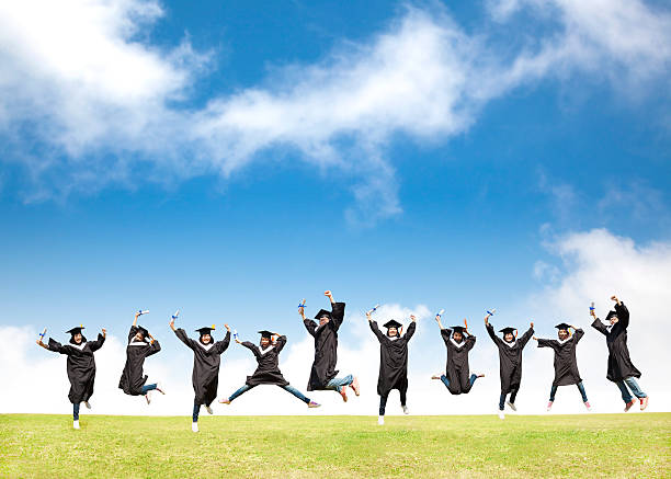 College students celebrate graduation and happy jump stock photo