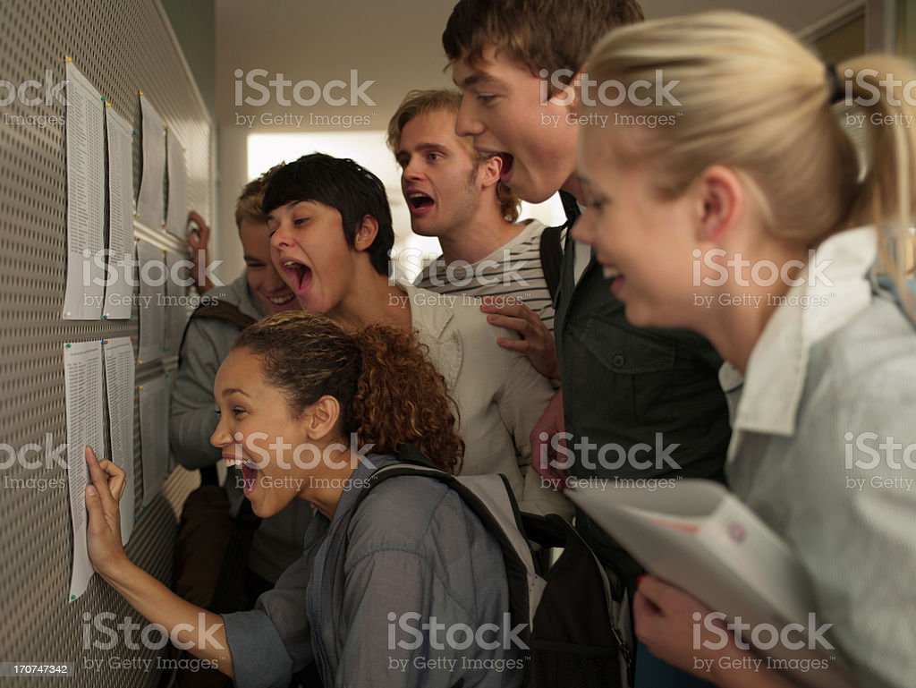College students checking test scores in corridor royalty-free stock photo