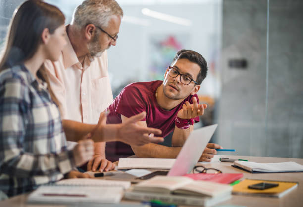 college students cooperating with their professor while e-learning at campus. - professor stock photos and pictures