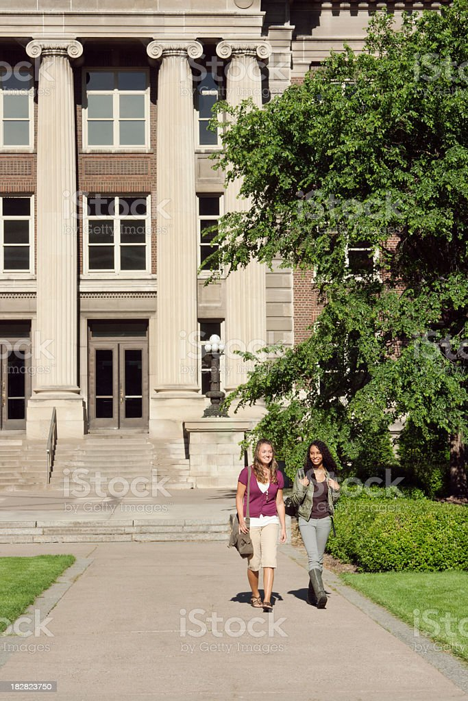 College Students, Friends Walking by Campus University Hall Educational Building stock photo