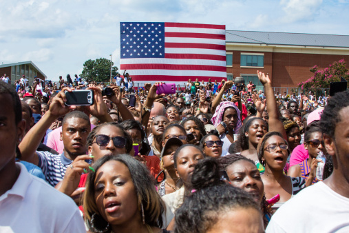 Norfolk, VA, USA - September 4th, 2012: Students cheer and take photos on their cell phones at the 2012 Barack Obama Presidential Campaign Rally at Norfolk State University, a historically black university.