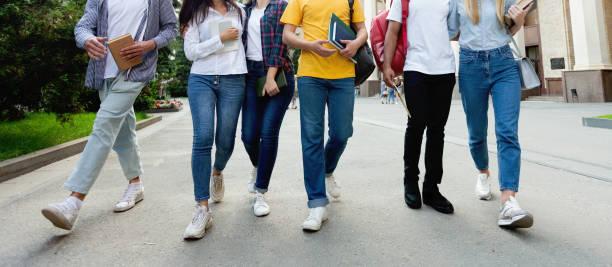 college students in high school campus walking during break - compagni scuola foto e immagini stock