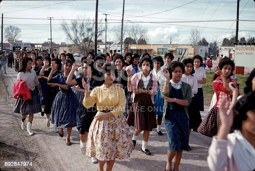 Texas, USA, 1960. A group of college students moving in a city (unfortunately unknown) in Texas. In the foreground, the Mexican-born young women dance a traditional Spanish dance. In the background the young men march after the women with rifles in their hands and in military order.