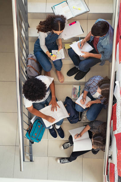 college students sitting on staircase at school and studying - esame maturità foto e immagini stock