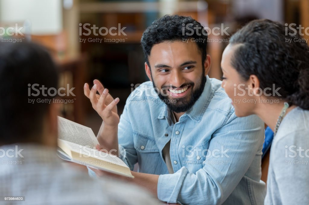 College students study together in campus library stock photo