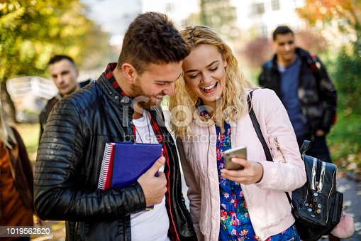 644191686 istock photo College students using mobile phone outdoors 1019562620