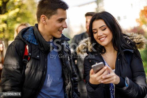 644191686 istock photo College students using mobile phone outdoors 1019562874