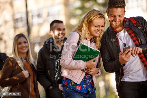 644191686 istock photo College students using mobile phone outdoors 1019565782