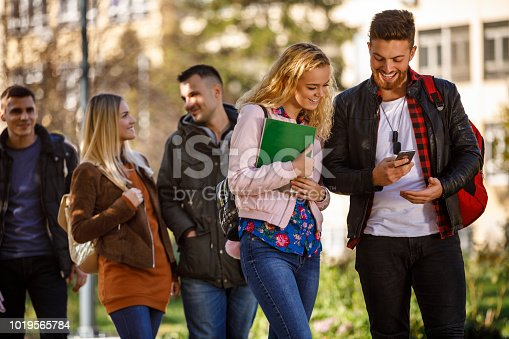 644191686 istock photo College students using mobile phone outdoors 1019565784