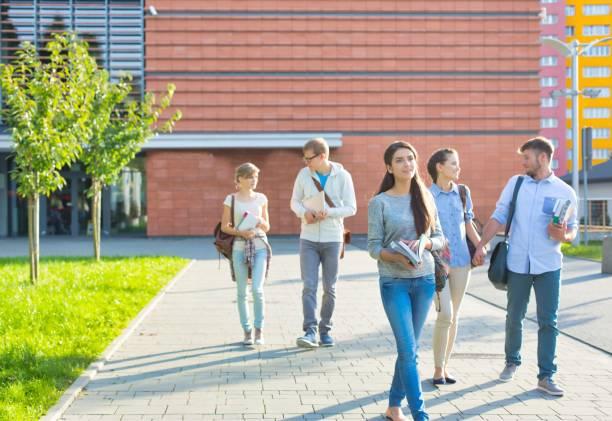 Estudiantes universitarios caminando fuera del campus - foto de stock