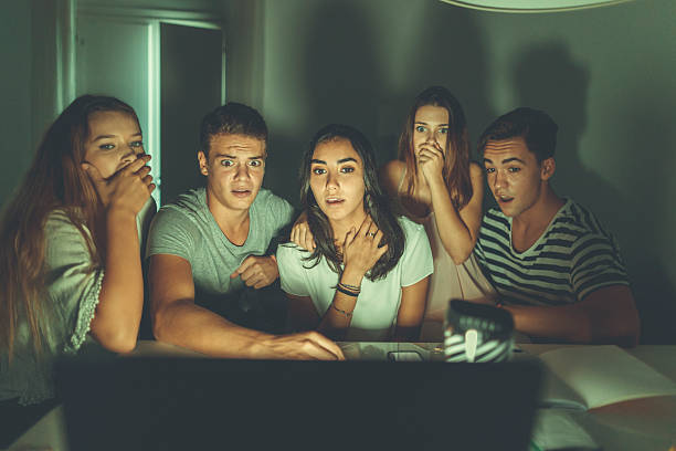 college students watching scary movie on laptop - jugendfilm stock-fotos und bilder