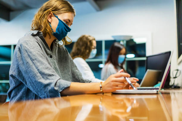 College Students Wearing Face Masks Working Together in Computer Lab Setting Three female college students; One in foreground in focus two female and one male blurred in background wearing face masks using technology working on laptops part of a series (Shot with Canon 5DS 50.6mp photos professionally retouched - Lightroom / Photoshop - original size 5792 x 8688 downsampled as needed for clarity and select focus used for dramatic effect) eyecrave stock pictures, royalty-free photos & images