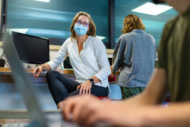 College Students Wearing Face Masks Working Together in Computer Lab Setting stock photo