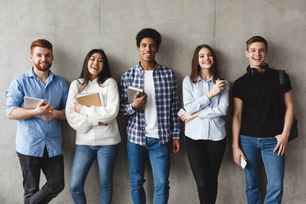 estudiantes universitarios con libros sonriendo a la cámara sobre la pared gris - estudiante fotografías e imágenes de stock