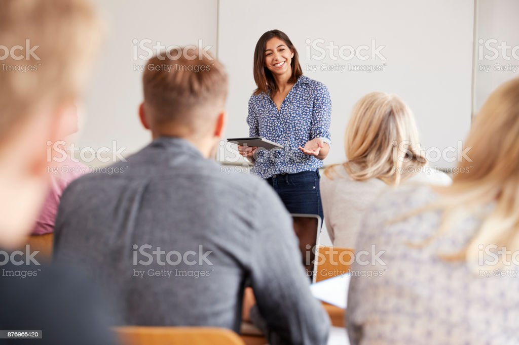 College Tutor With Digital Tablet Teaches Mature Students stock photo