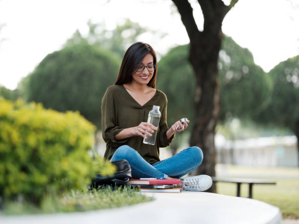 College woman sitting outdoors about to drink water stock photo