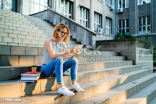 Young beautiful Caucasian female college student using tablet on a staircase.