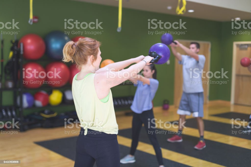College-age co-ed group do a class together a modern gym stock photo