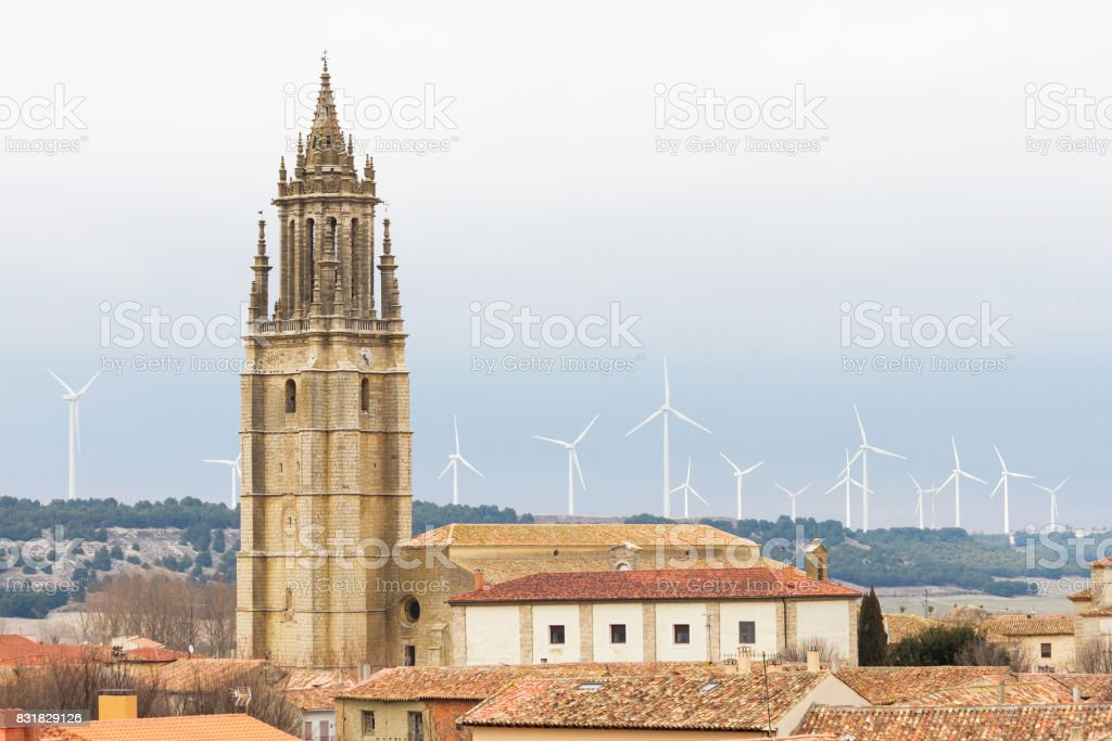 Collegiate tower in Ampudia with wind turbines in the background. Spain - Torre de la Colegiata en Ampudia con Aerogeneradores en segundo plano. España stock photo