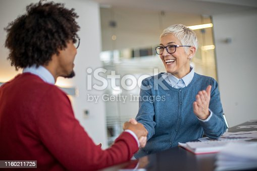 Mature gray haired woman and young businessman handshaking  and greeting at meeting in office.
