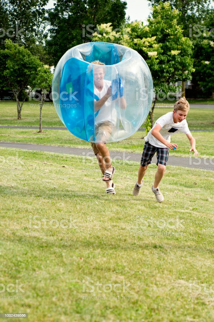 Collision between brothers playing in inflated balloon in suburb park. stock photo