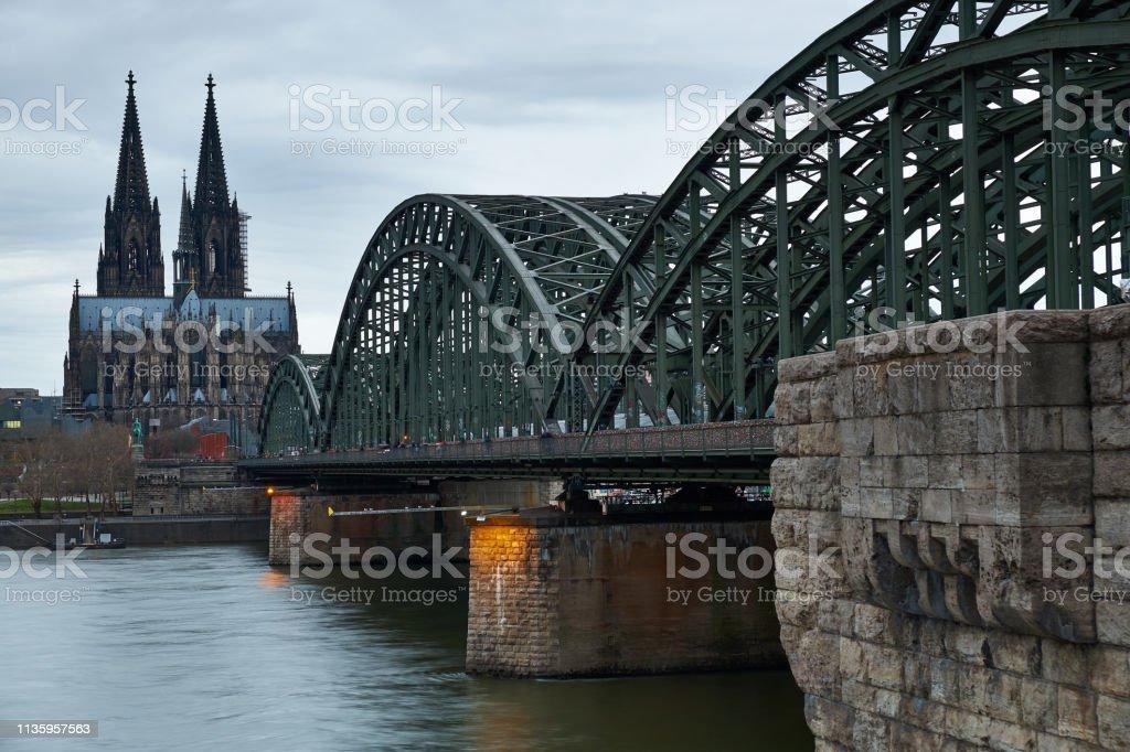 Kölner Dom und Hohenzollernbrücke am späten Abend. Bewölkter Himmel. Panorama aus Köln. – Foto