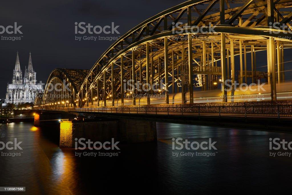 Kölner Dom bei Nacht Panorama während ein Zug über die Hohenzollernbrücke rauscht – Foto
