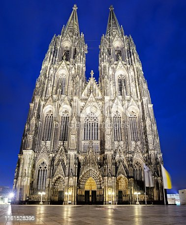 Portal and sculptures on facade of Cologne Cathedral at night, Germany. Composite photo