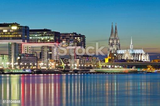 Illuminated Cologne Cathedral with the Rheinau Harbor (Rheinauhafen) buildings at night