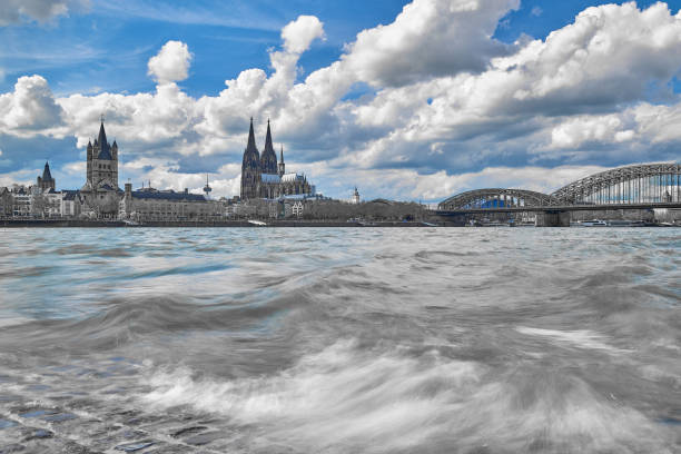 Kölner Dom, Groß St. Martin Kirche, Hohenzollernbrücke mit Blick über den Rhein mit altem römischen Pflaster im Vordergrund auf die Alstadt von Köln. Schwarz weiß Aufnahme mit blauem Himmel. – Foto