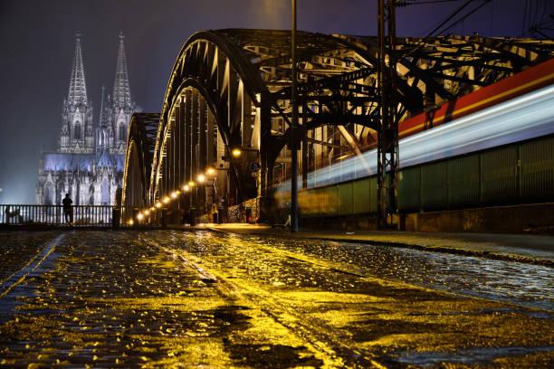 Kölner Dom Panorama mit Hohenzollernbrücke aus Bodenhöhe beim Regen und einem fahrendem Zug – Foto