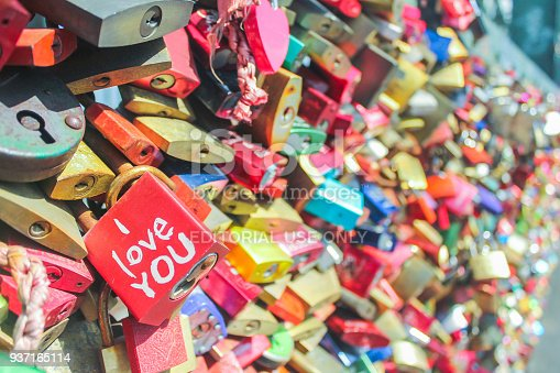 Cologne, Germany - April 14, 2015 : Multi colored love lock stacking in Cologne bridge. There's I Love You written on a red padlock. The focus is in the red padlock while the background is blurred.