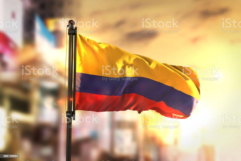 Bandera de Colombia contra la ciudad borrosa de fondo en contraluz amanecer - foto de stock
