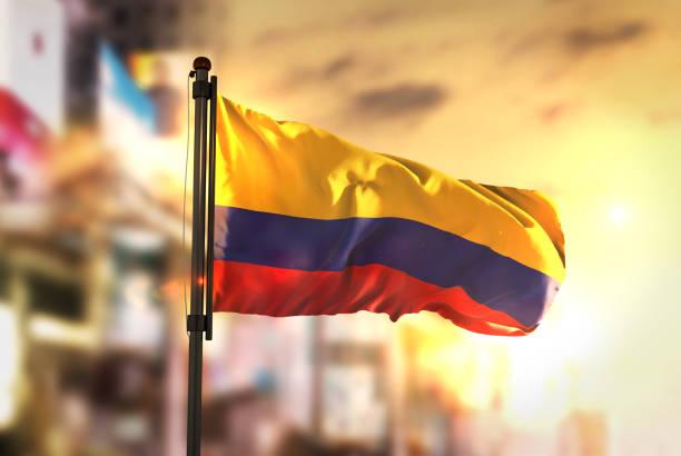 bandera de colombia contra la ciudad borrosa de fondo en contraluz amanecer - bandera colombiana fotografías e imágenes de stock