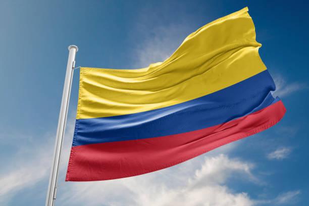 bandera de colombia está agitando contra el cielo azul - bandera colombiana fotografías e imágenes de stock