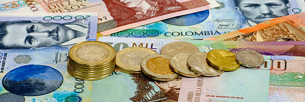 Colombia – Photograph Of Banknotes and CoinsFrom The Country Arranged With Coins Tipping Over And Finished As A Banner Style Image stock photo