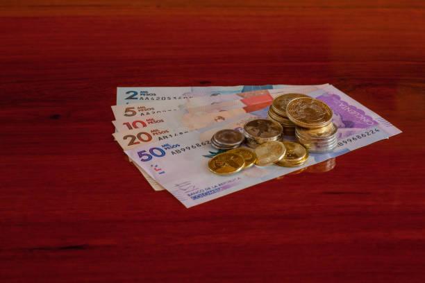 Kolumbien, Südamerika - International preisgekrönten glänzend kolumbianische Münzen auf die neuen Banknoten auf einem Palisander Tisch platziert. Textfreiraum – Foto