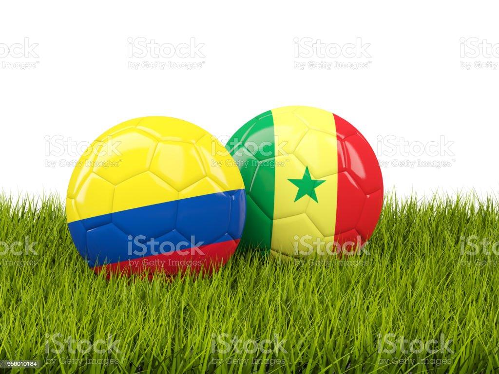 Colômbia vs Senegal. Conceito de futebol. Bolas de futebol com bandeiras na grama verde - foto de acervo