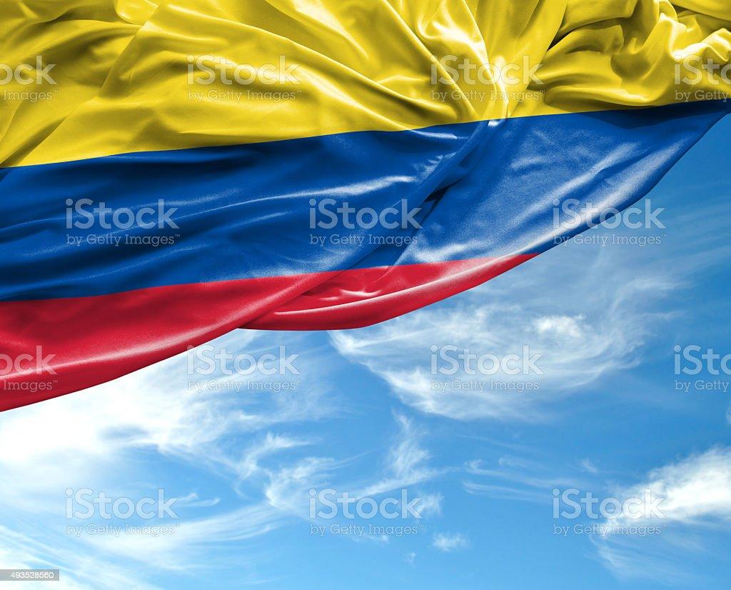 Bandera colombiana saludando con la mano en el hermoso día - foto de stock