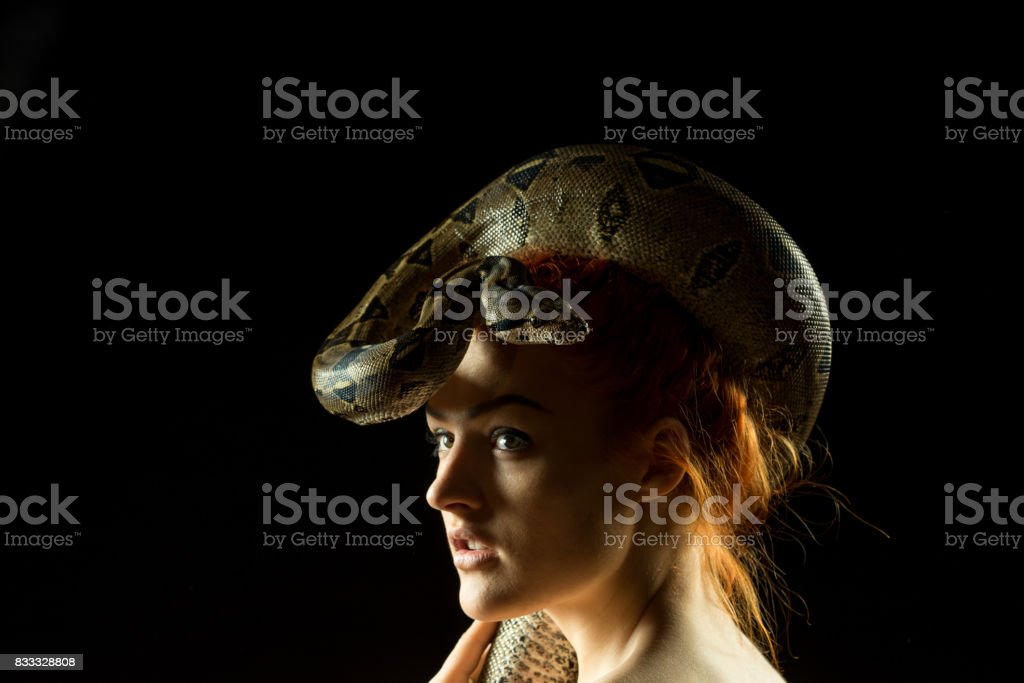 Colombian Boa and woman. Tropical brown constrictor around her head. Snake skin with yellow and black spots on a black background stock photo