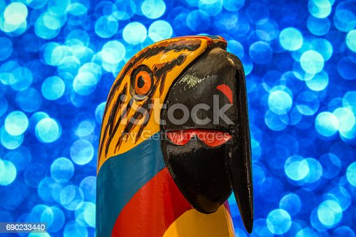 Small souvernir of a Colombian colorful parrot made of wood, with an electric blue bokeh as background