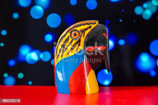 Small souvernir of a Colombian colorful parrot made of wood, with an electric blue bokeh as background and a red base