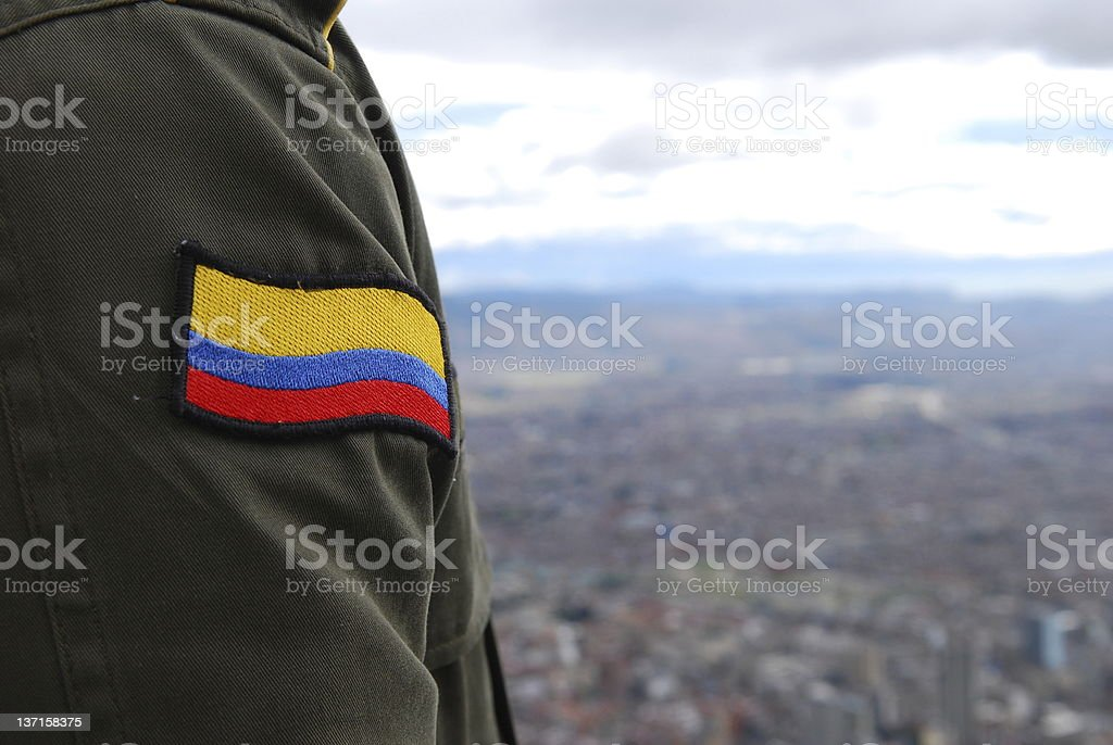 Colombian flag on soldier's uniform above Bogota royalty-free stock photo