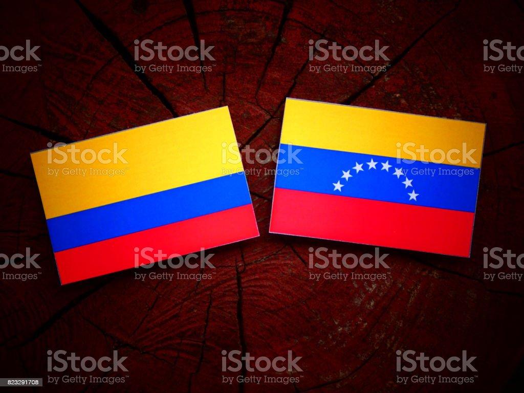 Bandera colombiana con bandera venezolana en un tocón de árbol aislado - foto de stock