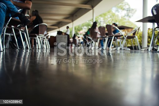 A low angle and defocused shot of a colombian university cafeteria, unrecognizable students can be seen during their lunch. Copy space included.