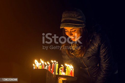 Happy Colombian woman lighting candles outdoors during the Noche de Velitas celebration that takes places on the 7th of December and marks the beginning of Christmas time