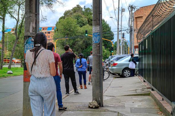 Kolumbianer beobachteten, wie sie vor einer Bank auf Carrera 15, wo sie die Calle 140 in der kolumbianischen Hauptstadt Bogota während der Covid-19-Situation im Land durchschneidet, Schlange stehen und die Guidlines in der Sozialverzückung nutzen. – Foto