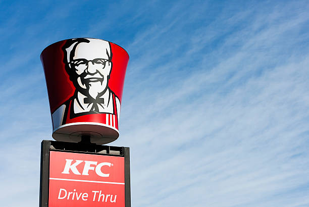 Colonel Sanders' image on bucket-shaped sign above KFC franchise stock photo