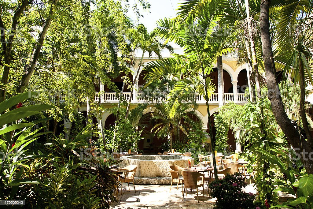 colonial architecture: lush courtyard with tables and fountain stock photo